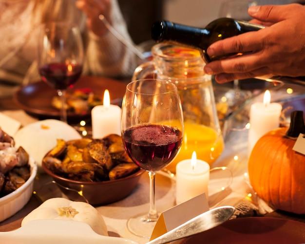 夕食時にワインを注ぐクローズアップ手