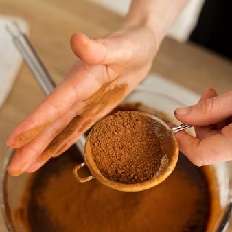 Chiuda sulle mani che preparano la miscela del cioccolato