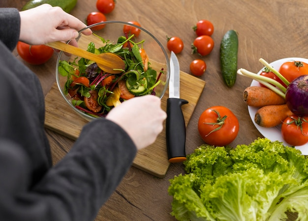 Chiudere le mani che preparano insalata