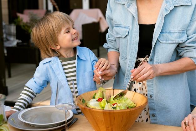 Mani ravvicinate che preparano l'insalata