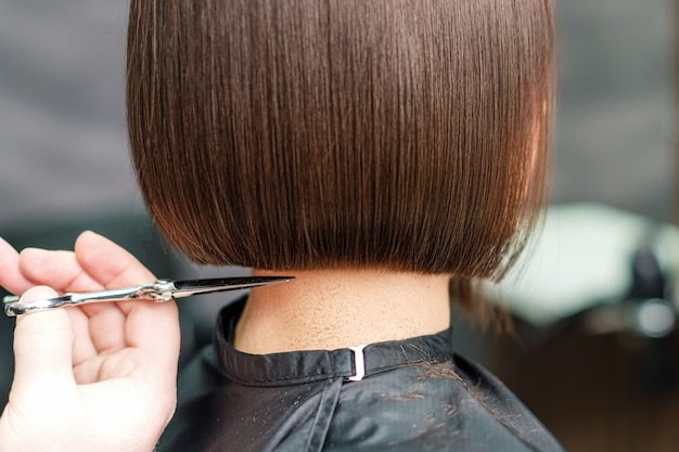 Close up hands of professional hair stylist cuts hair with scissors
