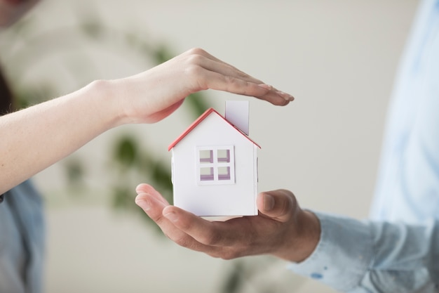 Close-up of hands protecting small house model