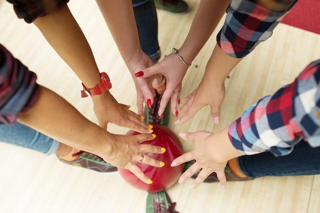 Руки крупным планом тянутся за шаром для боулинга.