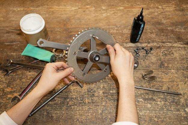 自転車の部品を修理する手をクローズアップ