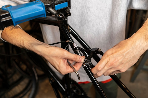 Chiuda sulle mani che riparano bici al negozio