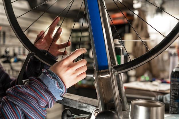 自転車のホイールを修理する手を閉じる