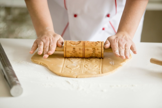 Close up of hands rolling gingerbread dough with patterned rolle