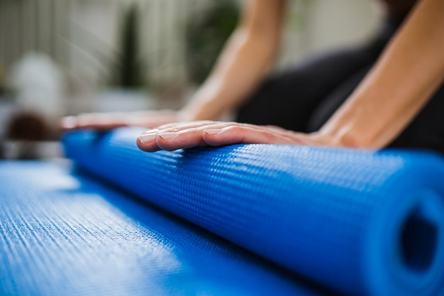 Close-up hands rolling up yoga mat