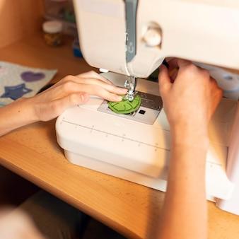 Крупным планом руки шитье материала