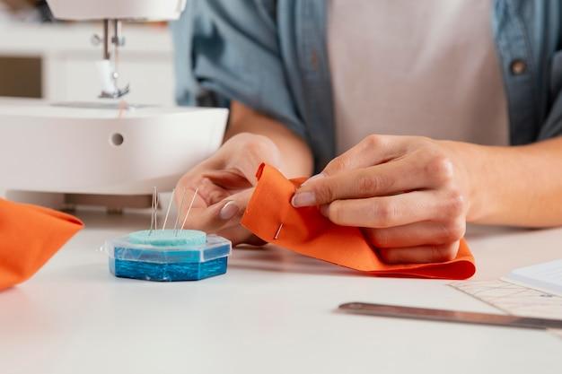オレンジ色の生地を縫うクローズアップの手