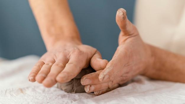 Mani del primo piano che modellano l'argilla