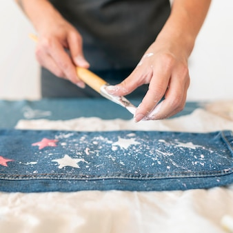 Mani del primo piano che spruzza jeans