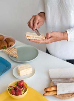 빵에 버터를 뿌리는 손을 닫습니다