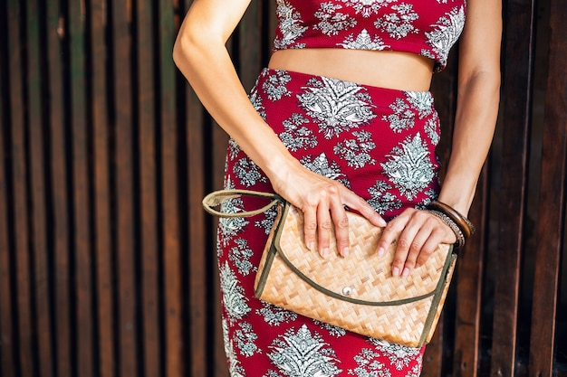 Chiudere le mani della donna alla moda tenendo la borsa di paglia
