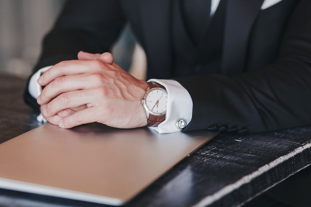 Close-up of the hands of a successful man with a watch and laptop. business concept