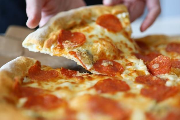 Крупным планом руки берут ломтик пиццы с сосисками