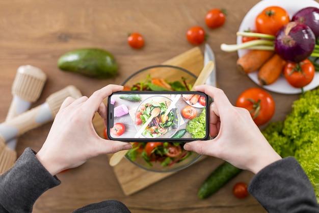 食べ物の写真を撮る手をクローズアップ