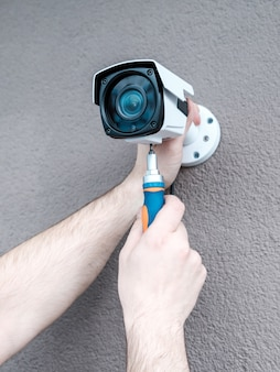 Close-up hands of technician adjusting cctv camera