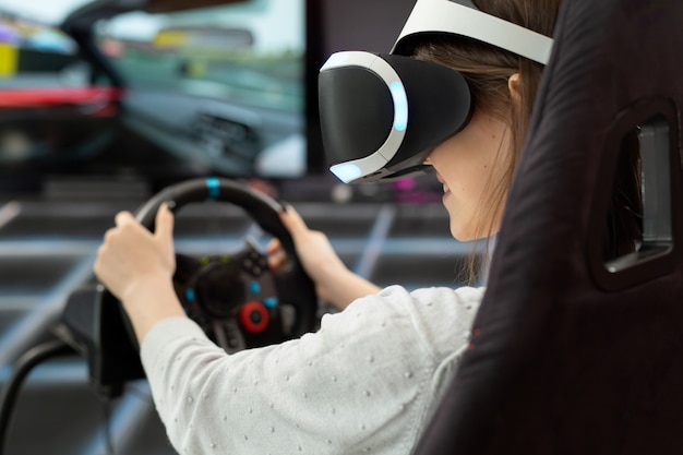 Close-up of the hands of a teenage girl in virtual reality glasses, who is holding the steering wheel and playing a computer game on the console.