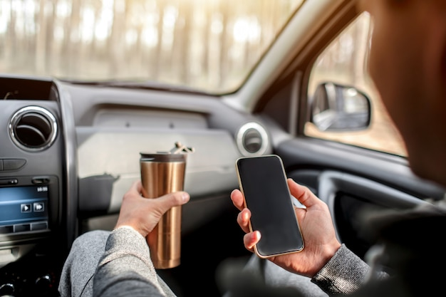 Close-up of hands and thermos with smartphone in car. travel concept