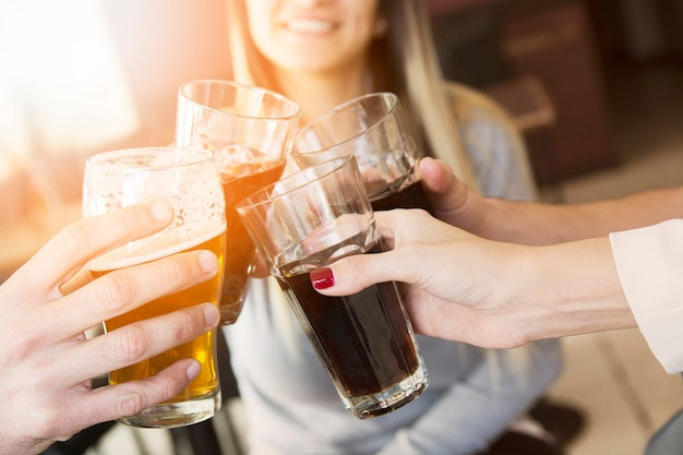 Close-up of hands toasting glasses of drinks