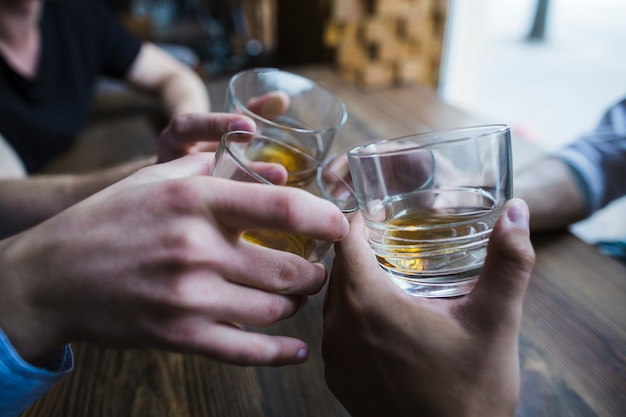 Close-up of hands toasting whisky glasses