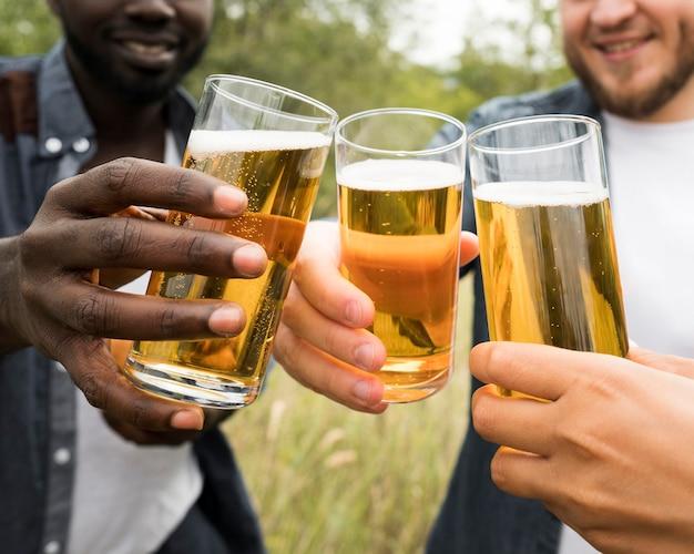 Крупным планом руки тосты с пивом