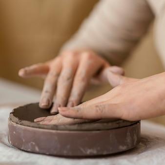 Mani del primo piano che toccano l'argilla