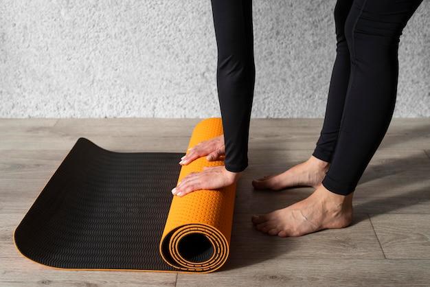 Mani del primo piano che toccano la stuoia di yoga