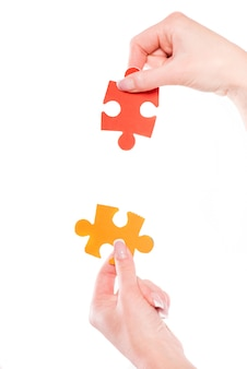 Close-up of hands trying to connect small jigsaw puzzles.