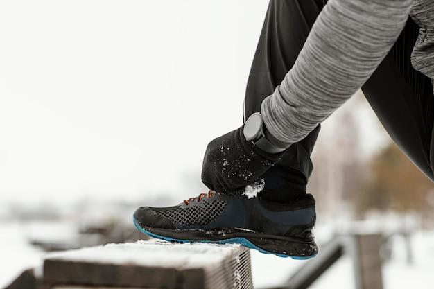 Mani del primo piano che legano la vista laterale dei lacci delle scarpe