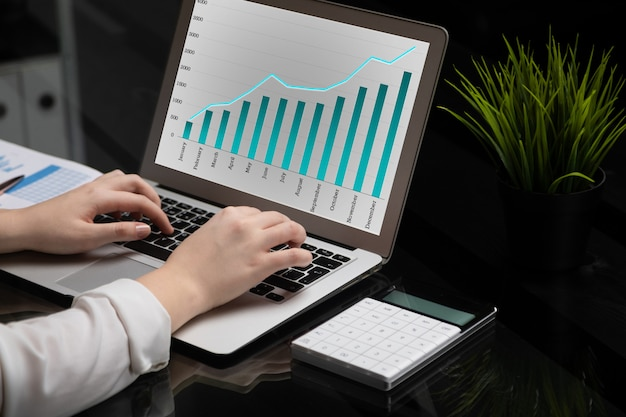 Close-up of hands typing on laptop with blank black screen next to charts and calculator