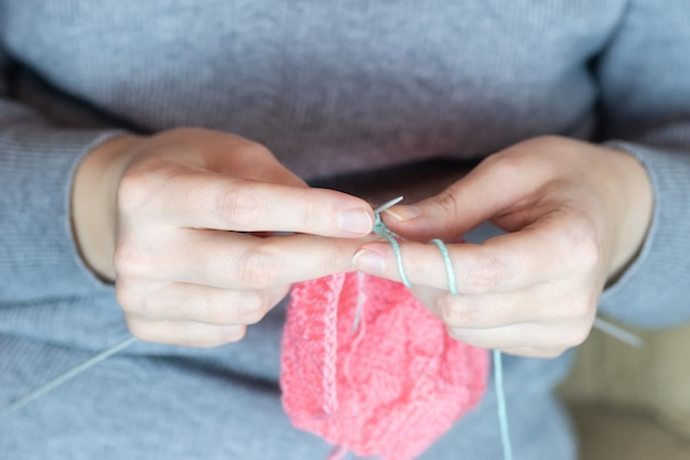 Close up of hands of unrecognizable woman knitting handmade clothes with spokes using pink wool yarn