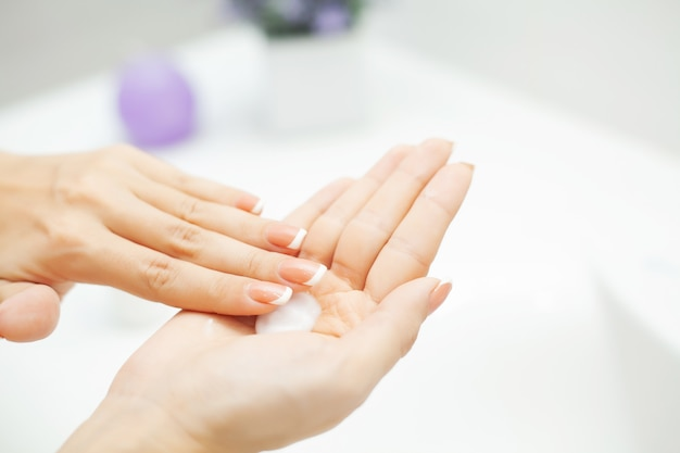 Close up hands use care products in light bathroom
