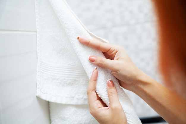 Крупным планом руки использовать белое полотенце в светлой ванной