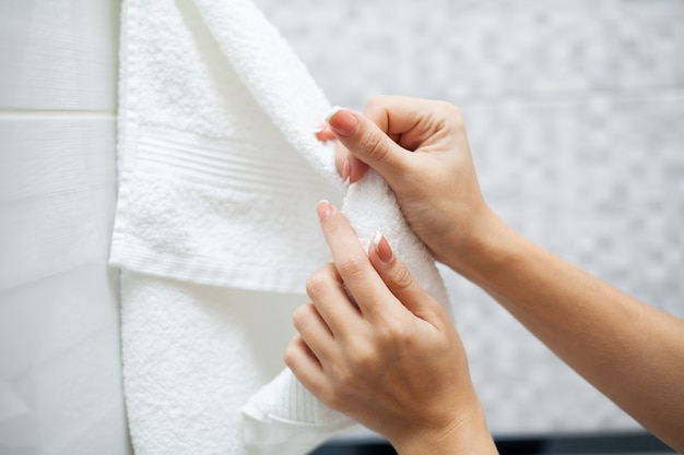 Close up hands use white towel in light bathroom