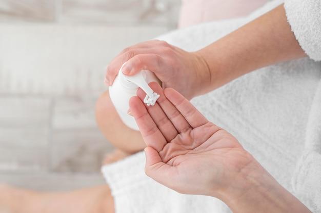 Mani del primo piano usando la crema