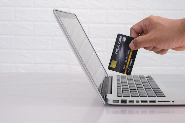 Close up of hands  using laptop and credit card in hand free from copy space. shopping/paying online concept.