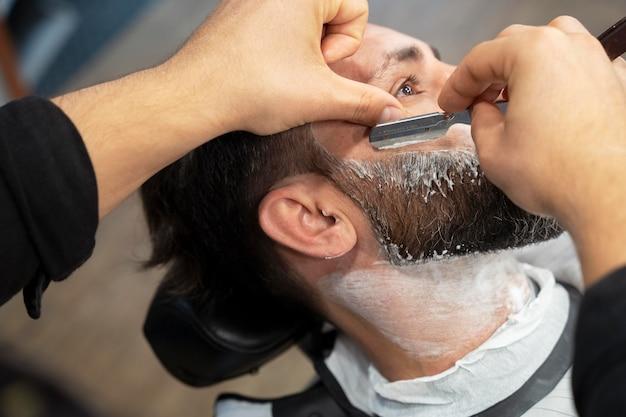 Close up hands using shaving blade