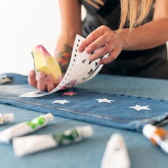 Mani del primo piano usando la spugna per dipingere