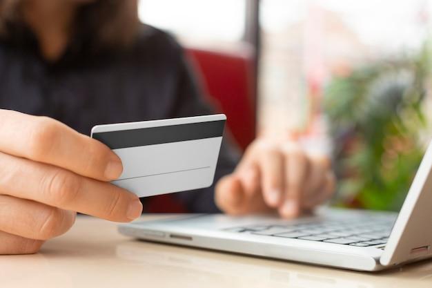 プラスチックカードで手を閉じます。ノートパソコンのキーボードでカード番号を入力します。オンライン支払いの概念。