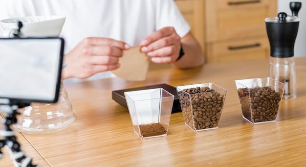 Mani del primo piano con chicchi di caffè