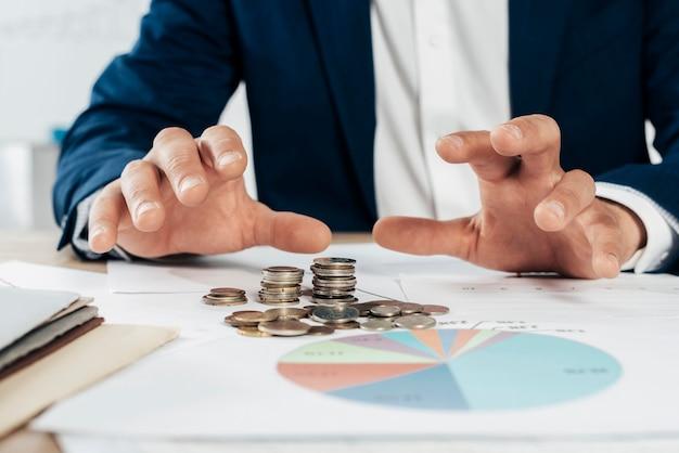Крупный план руки с монетами Premium Фотографии