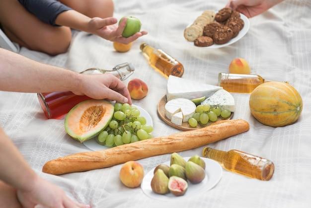 ピクニックで食べ物とクローズアップの手