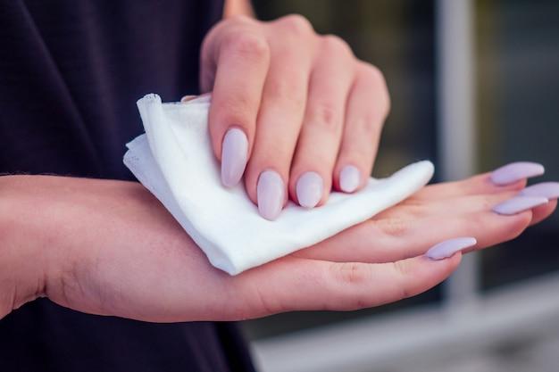 항균 젖은 냅킨 닦는 여자의 긴 손톱 매니큐어와 클로즈업 손