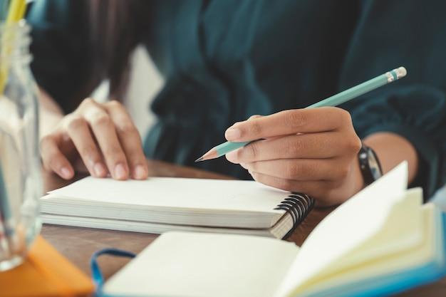 Закройте вверх руки с письменной перо на ноутбуке.