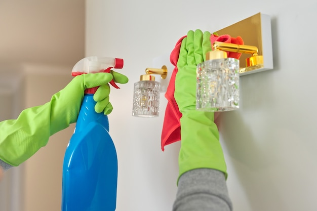 Close-up of hands with rag detergent, cleaning and polishing lamp