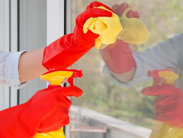 Close-up hands with rubber gloves cleaning the window