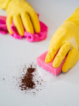 Close-up hands with rubber gloves disinfecting