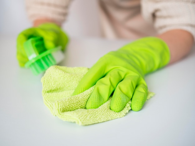 Close-up hands with rubber gloves holding cloth